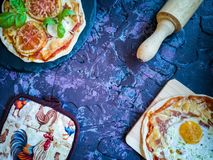 Homemade pizzas and utensils on dark background stock photography