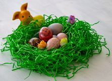 A homemade and plaited easter nest made from yeast dough with colorful Easter eggs and little chicks and Easter bunnies royalty free stock photos