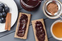 Homemade plum jam on rye crackers served with cocoa, cinnamon, t Stock Images