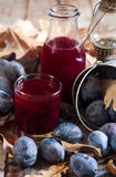 Homemade plum juice. With fresh prunes and fall leaves on wooden background Royalty Free Stock Images