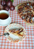 Homemade plum pie, autumn dessert with fresh plums, baking, healthy vegetarian food, a piece of cake on a plate, a cup stock image