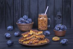 Homemade plum pie in plate, plum smoothies and raw plums on black wooden background. Close up Stock Photography
