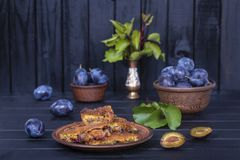 Homemade plum pie in plate and raw plums on black wooden background. Close up Stock Photos