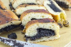 Homemade poppy seed sliced strudel  and a knife on a wooden boar Stock Images