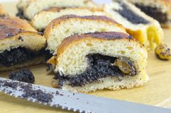 Homemade poppy seed sliced strudel  and a knife on a wooden boar Stock Photos