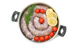 Homemade pork sausage in a frying pan for a roast. Royalty Free Stock Images