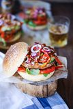 Homemade portobello mushroom burger. With red onions, roasted pepper, avocado and whitebean hummus royalty free stock image