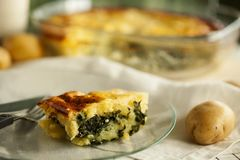 Homemade potato casserole with spinach and goat cheese. Close up. royalty free stock photo