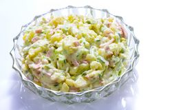 Homemade potato salad with green cucumber. Isolated stock image