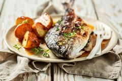 Homemade potatoes and seabream with cherry tomatoes and thyme. On old table stock photography