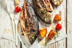 Homemade potatoes and seabream with herbs and tomatoes. On old table royalty free stock images