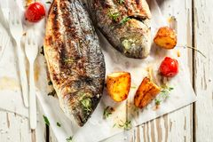 Homemade potatoes and seabream with tomatoes on white table. Closeup of Homemade potatoes and seabream with tomatoes on white table royalty free stock photos