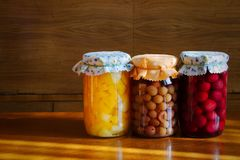 Homemade preserved fruit in jar,  organic food. Homemade preserved fruit in jar, conserved fruit in glass on wooden table, stored homegrown cherries Royalty Free Stock Photo