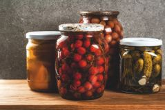Homemade preserving, canning food. Pickled or fermented vegetables in glass jars over kitchen drawer, grey stone wall background, copy space Stock Image