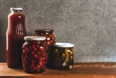 Homemade preserving, canning food. Pickled or fermented vegetables in glass jars over kitchen drawer, grey stone wall background, copy space Stock Photos