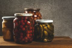 Homemade preserving, canning food. Pickled or fermented vegetables in glass jars over kitchen drawer, grey stone wall background, copy space Stock Photo