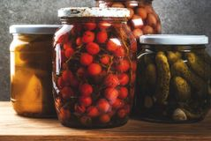 Homemade preserving, canning food. Pickled or fermented vegetables in glass jars over kitchen drawer, grey stone wall background, copy space Royalty Free Stock Photos