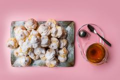 Homemade profiteroles served on a plate with a cup of tea on a pink background. Flat lay. royalty free stock photography