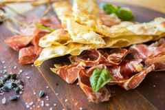 Homemade prosciutto and basil on a wooden board Royalty Free Stock Photography