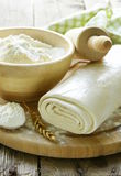 Homemade puff pastry and flour. On a wooden board Stock Photography