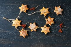 Homemade puff pastry in the form of a star on a string on a blue wooden background with berries. royalty free stock photos
