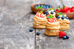 Homemade puff pastry stuffed with cream and berries on the rusti Royalty Free Stock Image