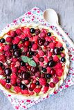 Homemade puff pastry sweet pizza pi with mascarpome cream cheese, fresh raspberry, strawberry, cherry, black currant decorated wit. H fresh mint on a wooden Stock Image