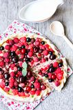 Homemade puff pastry sweet pizza pi with mascarpome cream cheese, fresh raspberry, strawberry, cherry, black currant decorated wit. H fresh mint on a wooden Stock Photos