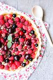 Homemade puff pastry sweet pizza pi with mascarpome cream cheese, fresh raspberry, strawberry, cherry, black currant decorated wit. H fresh mint on a wooden Royalty Free Stock Photos