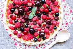 Homemade puff pastry sweet pizza pi with mascarpome cream cheese, fresh raspberry, strawberry, cherry, black currant decorated wit. H fresh mint on a wooden royalty free stock images