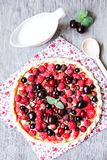 Homemade puff pastry sweet pizza pi with mascarpome cream cheese, fresh raspberry, strawberry, cherry, black currant decorated wit. H fresh mint on a wooden Stock Photography