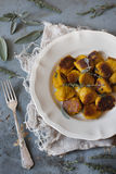 Homemade pumpkin dumplings on plate with thyme sprigs and sage leafs Stock Photos