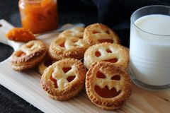 Homemade pumpkin Jam cookie for Halloween with funny faces. Snack with milk royalty free stock image