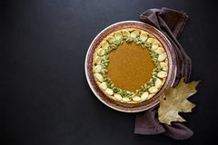 Homemade pumpkin pie with cinnamon on dark wooden background.