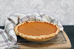 Homemade pumpkin pie on a cooling rack with towel wrap. Royalty Free Stock Images