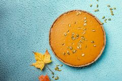 Homemade Pumpkin Pie. Fresh round bright orange homemade pumpkin pie on turquoise background, top view with copy space Stock Images