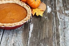 Homemade Pumpkin Pie in Red Dish. Homemade pumpkin pie in red ceramic pie plate over a rustic wooden background. Extreme shallow depth of field with selective stock images