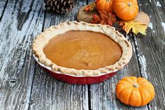 Homemade Pumpkin Pie in Red Pie Plate. Homemade pumpkin pie in red ceramic pie plate over a rustic wooden background. Extreme shallow depth of field with stock photos