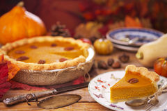 Homemade pumpkin pie on a rustic table with autumn decorations Royalty Free Stock Photo