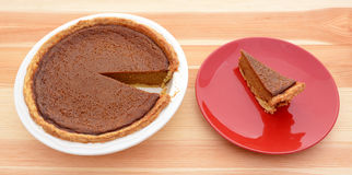 Homemade pumpkin pie with a slice served Stock Photography