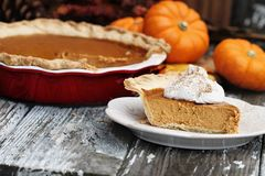 Homemade Pumpkin Pie Slice with Whiiped Cream. Slice of homemade pumpkin pie over a rustic wooden background. Extreme shallow depth of field with selective focus royalty free stock photos