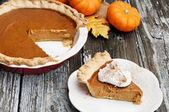 Homemade Pumpkin Pie Slice with Whiiped Cream. Slice of homemade pumpkin pie over a rustic wooden background. Extreme shallow depth of field with selective focus royalty free stock photo