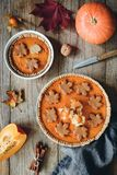 Homemade pumpkin pies on old wooden table. Stock Images