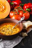 Homemade pumpkin soup in brown bowl on rustic table Stock Photography