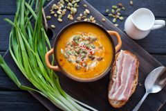 Homemade pumpkin soup with cream, bread, bacon and pumpkin seeds on a wooden background. Top viev stock photo
