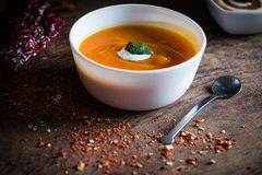 Homemade pumpkin soup with cream and parsley on a wooden background Royalty Free Stock Photo