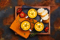 Homemade pumpkin soup in retro enamel mugs Royalty Free Stock Image