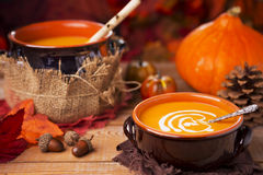 Homemade pumpkin soup on a rustic table with autumn decorations Royalty Free Stock Photos