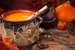 Homemade pumpkin soup on a rustic table with autumn decorations Stock Images