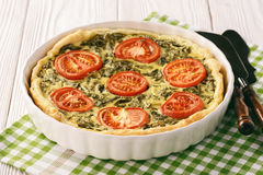 Homemade quiche with spinach, feta cheese and tomatoes. Royalty Free Stock Photography